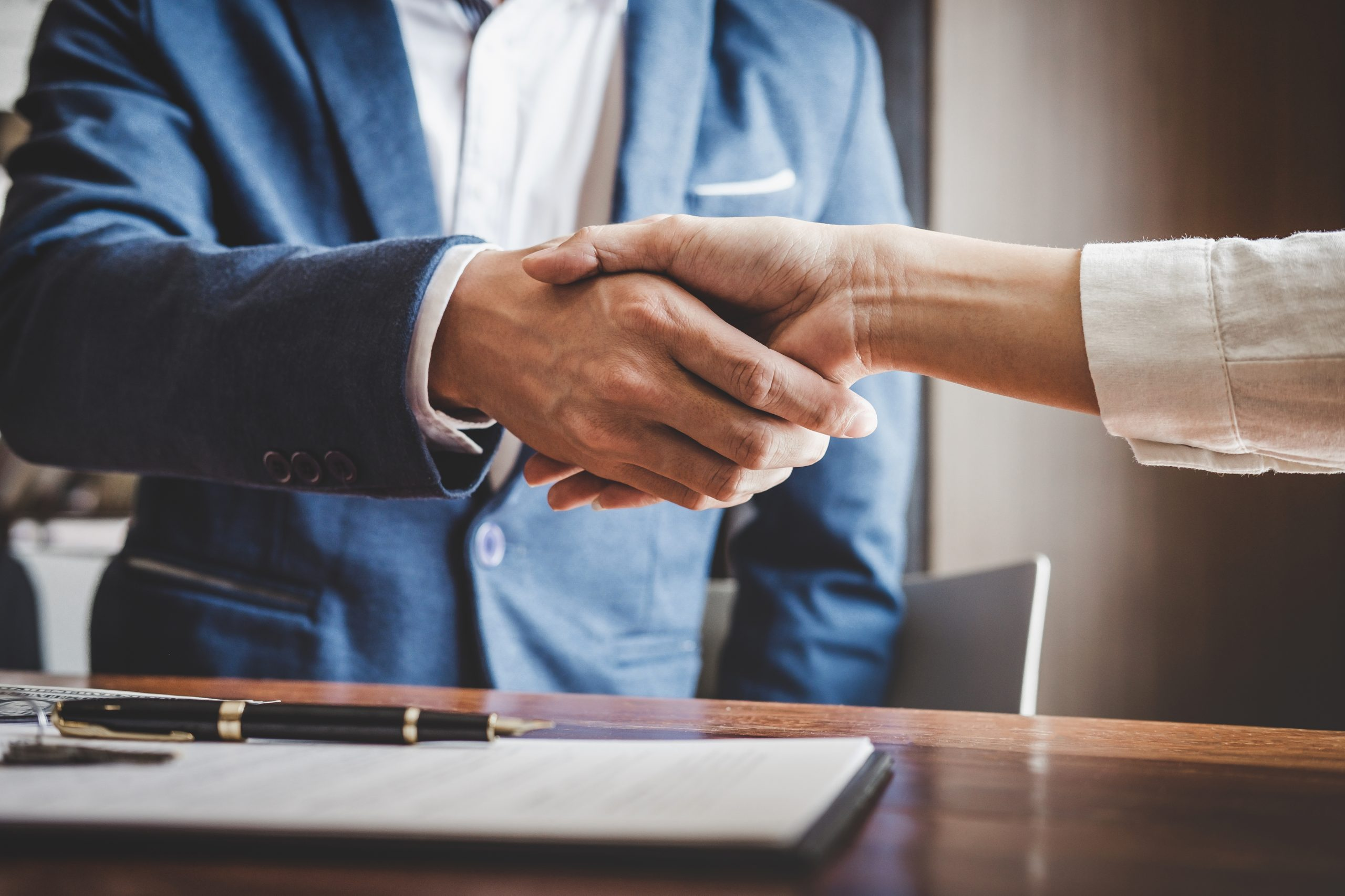 two men shaking hands over a signed private lender loan contract