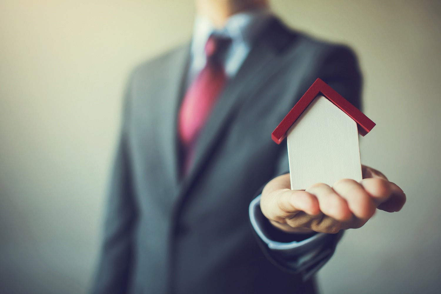 Businessman In Suit Holding out mini house