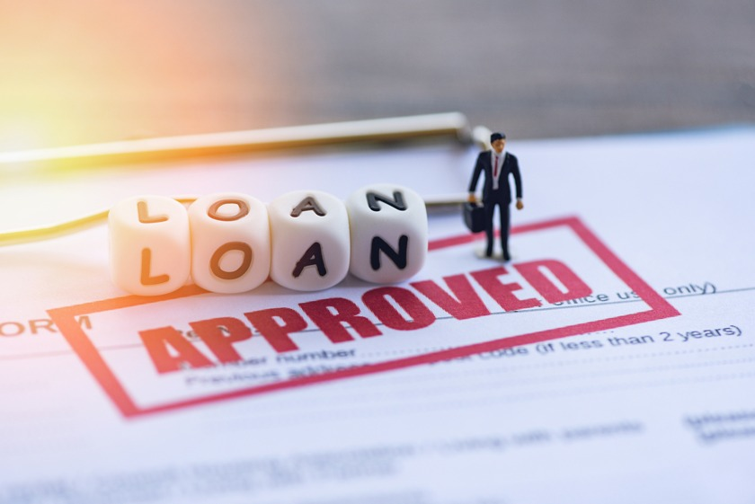 Loan Approval Businessman figure standing on top of a loan application stamped approved