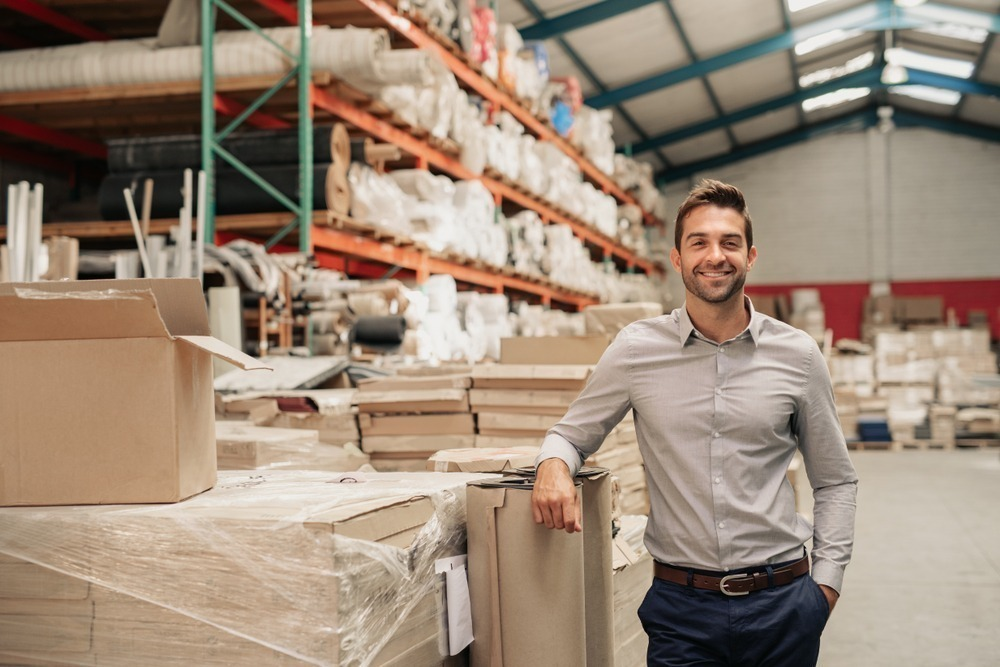 Portrait of a smiling warehouse manager leaning against some stock with piles of carpets stacked on shelves in the background