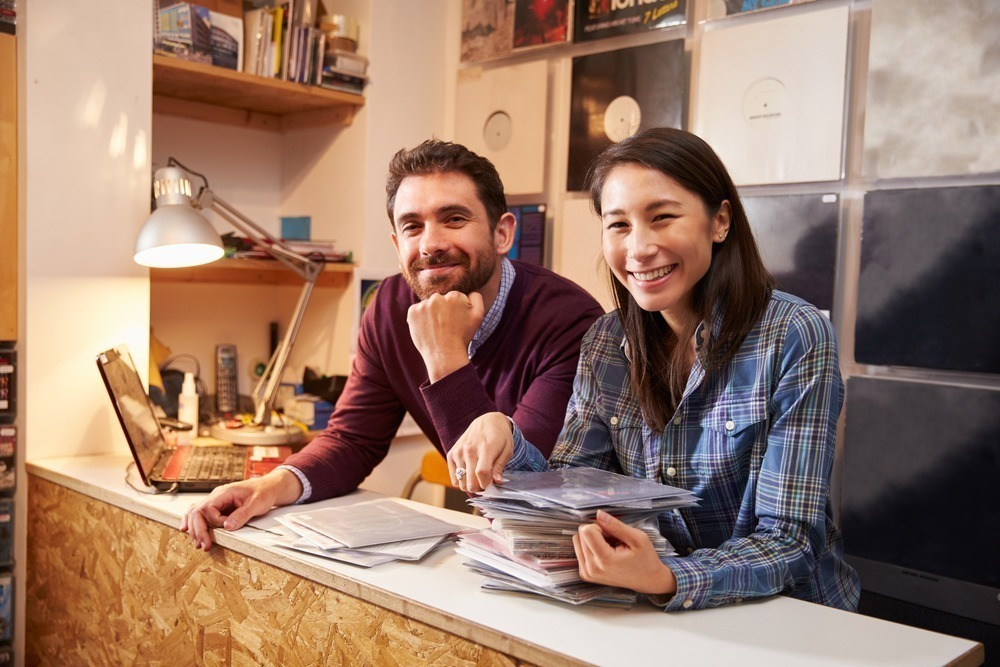 A smiling couple behind the counter in their record store business