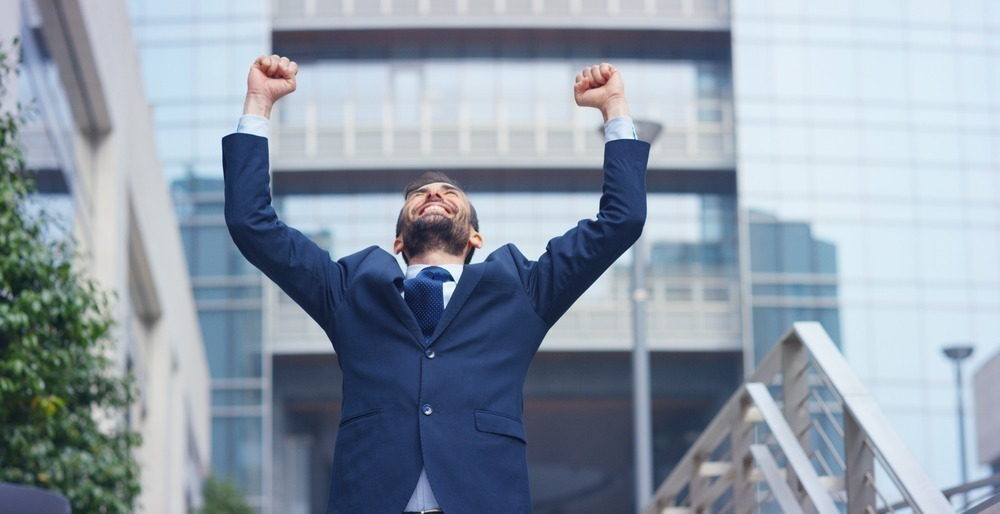 Businessman celebrating with hands in air and smiling