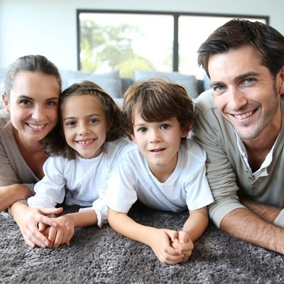 Family smiling, laying on floor